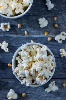 Vista dall'alto di popcorn in una ciotola bianca con un blu. con popcorn.