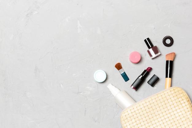 Vista dall'alto di prodotti di bellezza caduti dalla borsa di cosmetici su cemento