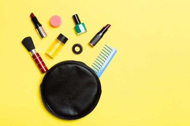 Vista dall'alto di prodotti di bellezza caduti dalla borsa di cosmetici su giallo.