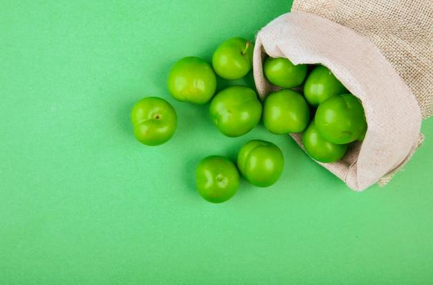 Vista dall'alto di prugne acide verdi sparse da un sacco sul tavolo verde