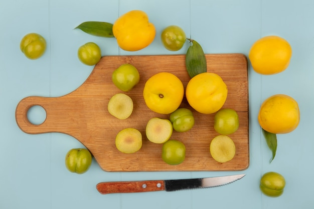 Vista dall'alto di prugne ciliegie verdi fresche su una tavola di cucina in legno con pesche gialle fresche su sfondo blu