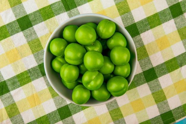 Vista dall'alto di prugne verdi acide in una ciotola bianca sul tavolo in tessuto plaid