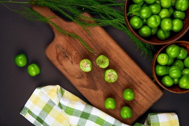 Vista dall'alto di prugne verdi affettate cosparse di menta piperita secca su un tagliere di legno e ciotole di legno piene di prugne verdi sul tavolo nero