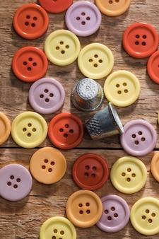 Vista dall'alto di pulsanti con ditali su superficie di legno