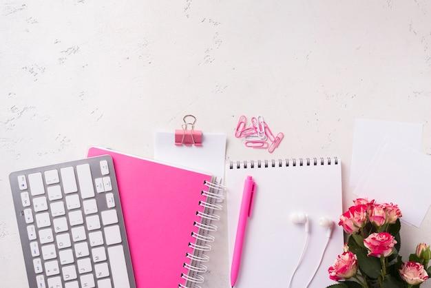 Vista dall'alto di quaderni sulla scrivania con bouquet di rose e copia spazio