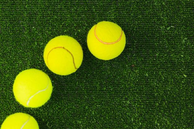 Vista dall'alto di quattro palle di racchetta su erba verde