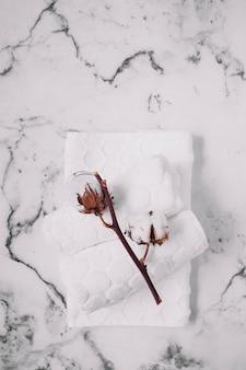 Vista dall'alto di ramoscello di cotone e tovaglioli bianchi su sfondo di marmo