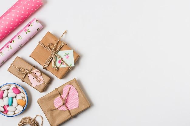 Vista dall'alto di regali con carta da imballaggio e caramelle
