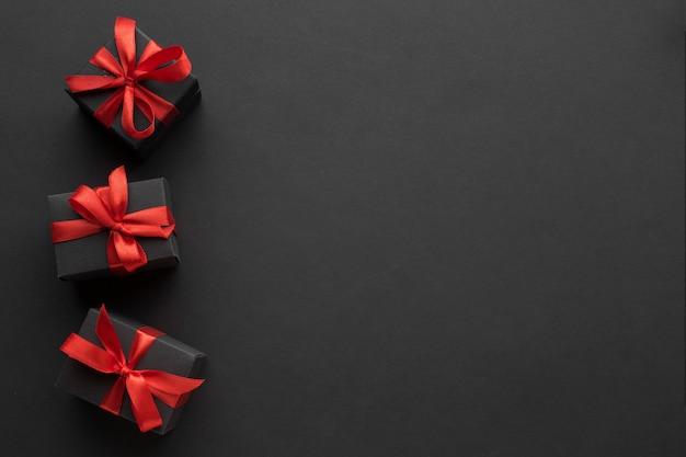 Vista dall'alto di regali eleganti con nastro rosso