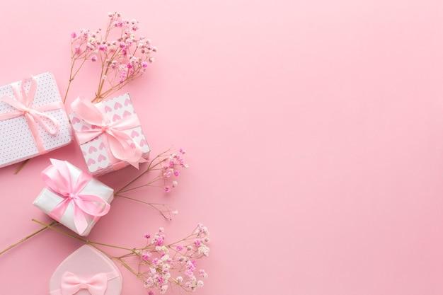 Vista dall'alto di regali rosa con fiori e copia spazio
