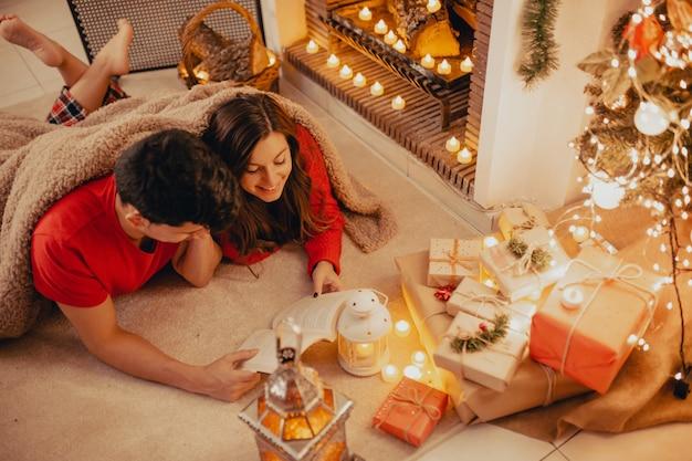 Vista dall'alto di relax coppia coperta da una coperta morbida e accogliente a casa leggendo un libro insieme sotto il camino con candele, regali e albero decorato.