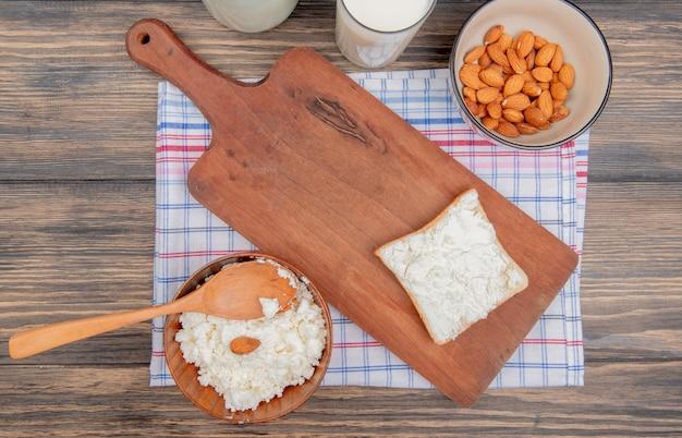 Vista dall'alto di ricotta con cucchiaio di legno in ciotola e latte di mandorle in ciotola con fetta di pane sul tagliere sul panno plaid e tavolo in legno