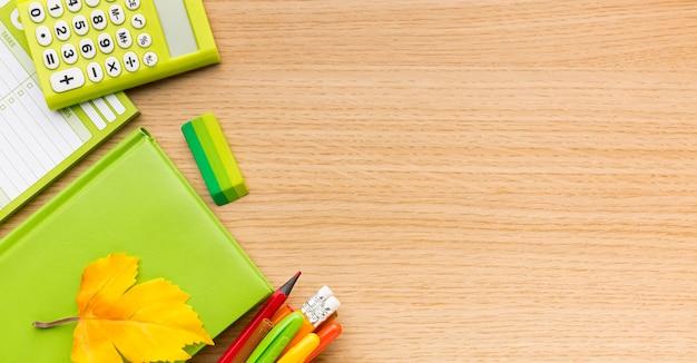 Vista dall'alto di ritorno a materiale scolastico con copia spazio e libro