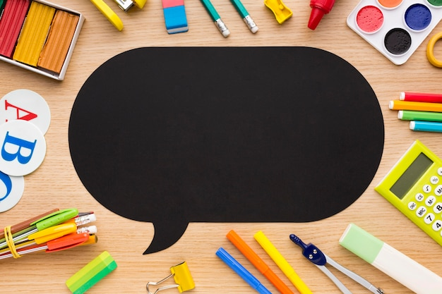 Vista dall'alto di ritorno a materiale scolastico con matite e bolla di chat
