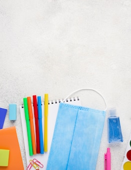 Vista dall'alto di ritorno a materiale scolastico con matite e maschera medica