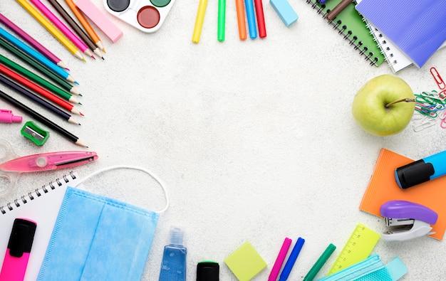 Vista dall'alto di ritorno a materiale scolastico con matite e mela