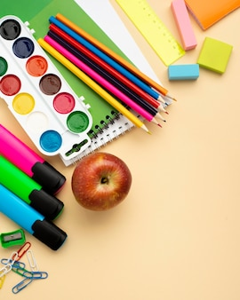 Vista dall'alto di ritorno a scuola di articoli di cancelleria con mela e matite colorate