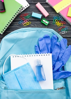Vista dall'alto di ritorno a scuola di articoli di cancelleria con zaino e notebook