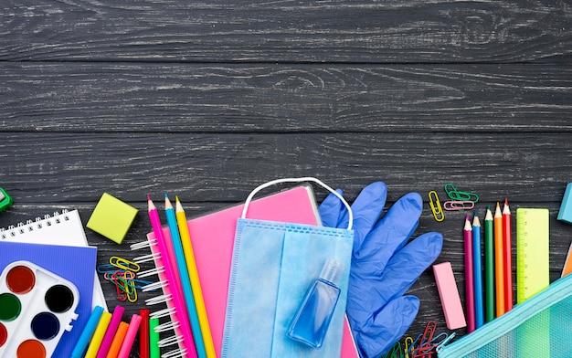 Vista dall'alto di ritorno a scuola di cancelleria con matite multicolori e mascherina medica
