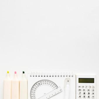 Vista dall'alto di ritorno a scuola elementi essenziali con calcolatrice e taccuino