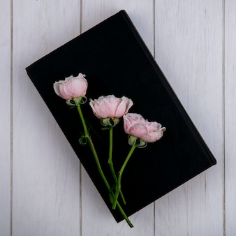 Vista dall'alto di rose rosa chiaro su un libro nero su una superficie grigia