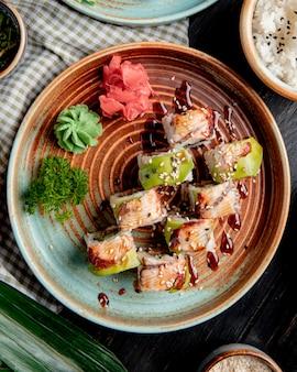 Vista dall'alto di rotoli di sushi con anguilla avocado e cetriolo con zenzero e wasabi su un piatto su legno