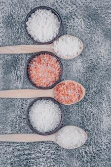 Vista dall'alto di sale in ciotole e cucchiai di legno con sale himalayano