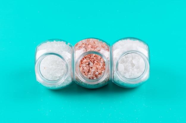 Vista dall'alto di sale in piccoli vasetti con sale himalayano su ciano sfondo blu. orizzontale
