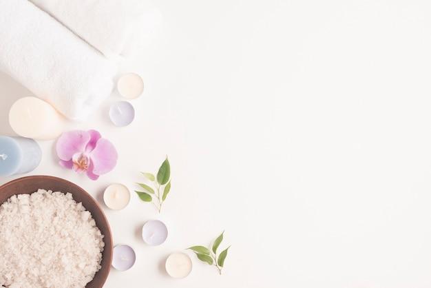Vista dall'alto di sale marino in ciotola di argilla con orchidea, candele e asciugamano arrotolato su sfondo bianco