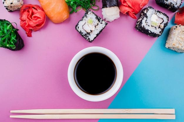 Vista dall'alto di salsa di soia e involtini di sushi
