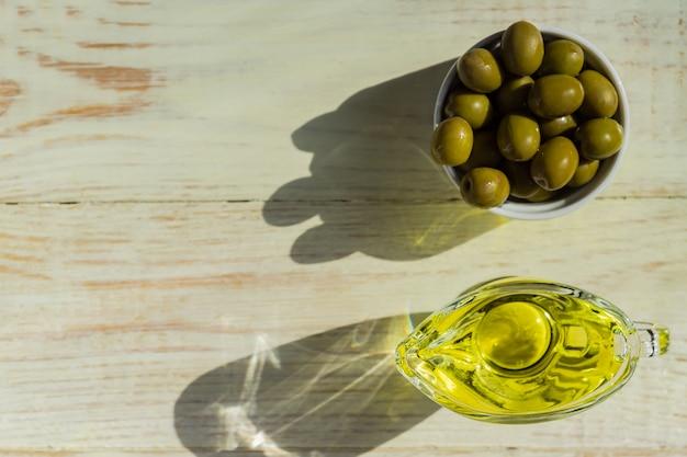 Vista dall'alto di salsa di vetro con olio extra vergine di oliva e olive verdi fresche sul tavolo di legno.
