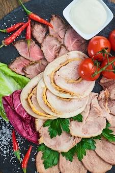 Vista dall'alto di salumi arrosto di manzo, prosciutto cotto, involtino di pollo e lingua di manzo, servito su una tavola di pietra