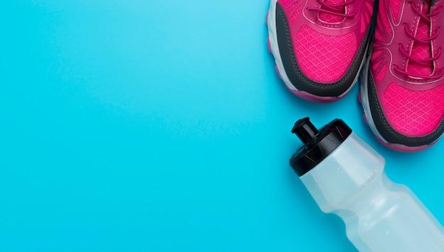 Vista dall'alto di scarpe da ginnastica con copia spazio e bottiglia d'acqua