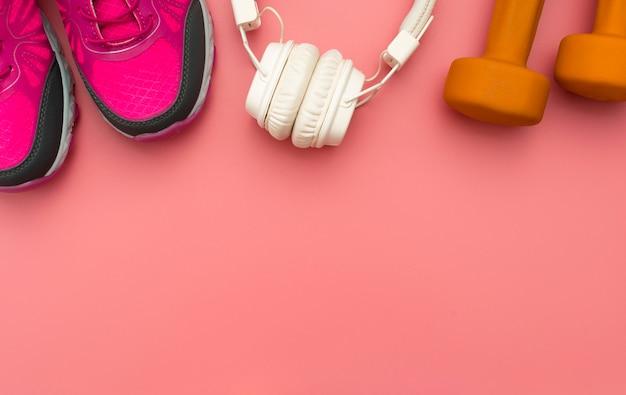 Vista dall'alto di scarpe da ginnastica con cuffie e pesi