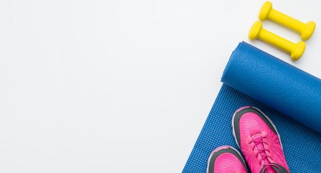 Vista dall'alto di scarpe da ginnastica con pesi e spazio di copia