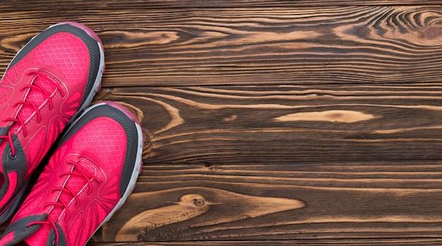 Vista dall'alto di scarpe da ginnastica su fondo in legno con spazio di copia