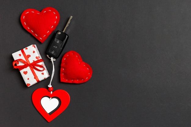 Vista dall'alto di scatola regalo, chiave auto, cuori in legno e tessuto
