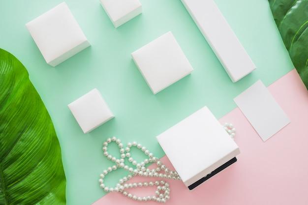 Vista dall'alto di scatole bianche con perle e foglie su sfondo colorato