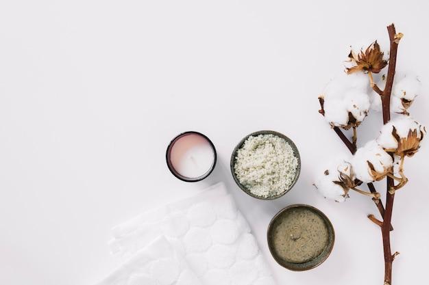 Vista dall'alto di scrub; candela; tovagliolo e ramoscello di cotone su superficie bianca