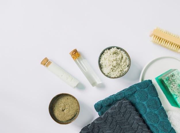 Vista dall'alto di scrub cosmetico alle erbe; spazzola; tovagliolo e saponetta sulla superficie bianca