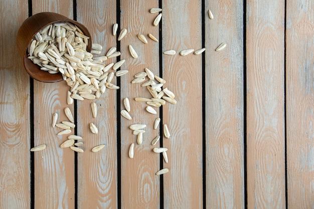 Vista dall'alto di semi di girasole bianchi sparsi da un vaso di terracotta