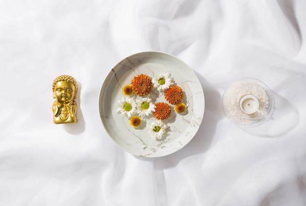 Vista dall'alto di sfondo tessuto voile con un piatto con fiori galleggianti