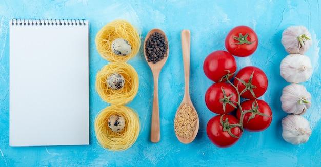 Vista dall'alto di sketchbook nido di pasta gialla con piccole uova di quaglia cucchiai di legno con pasta a forma di stella e pepe mais pomodori freschi e aglio su blu