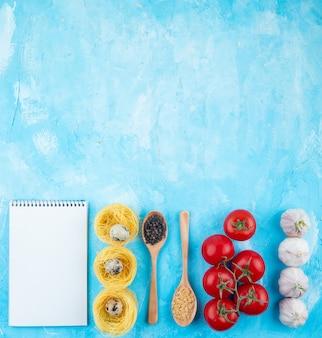 Vista dall'alto di sketchbook nido di pasta gialla con piccole uova di quaglia cucchiai di legno con pasta a forma di stella e pepe mais pomodori freschi e aglio su sfondo blu