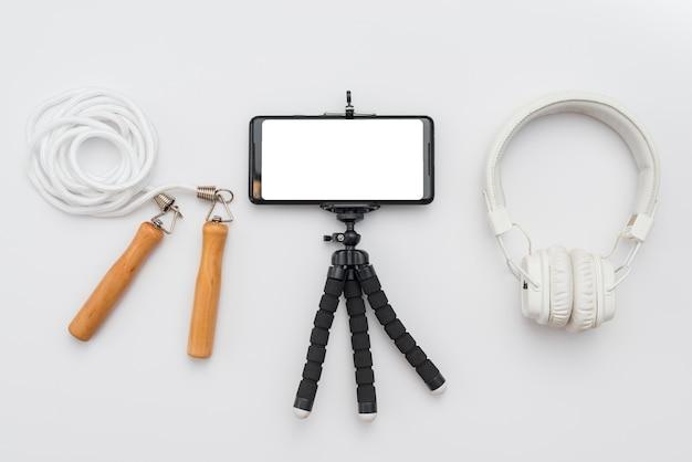 Vista dall'alto di smartphone con treppiede e corda per saltare