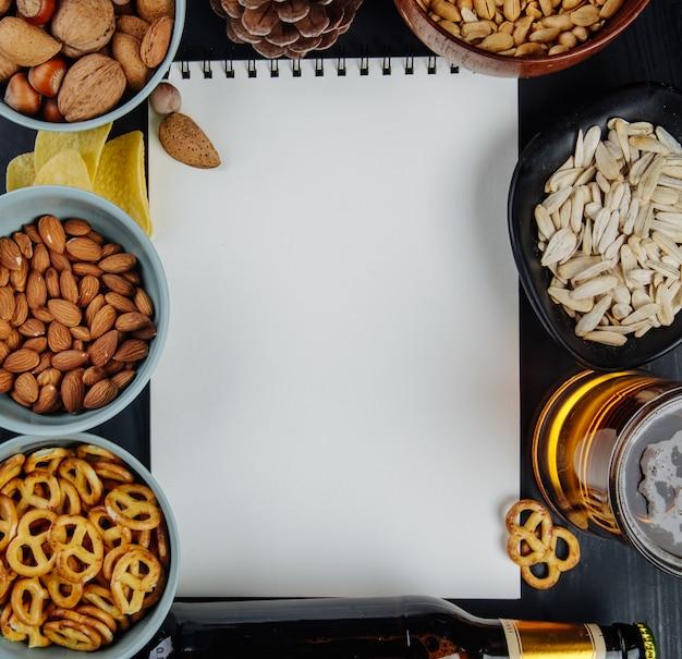 Vista dall'alto di snack salati mini salatini arachidi mandorle semi di girasole e patatine con sketchbook bianco e un boccale di birra su nero