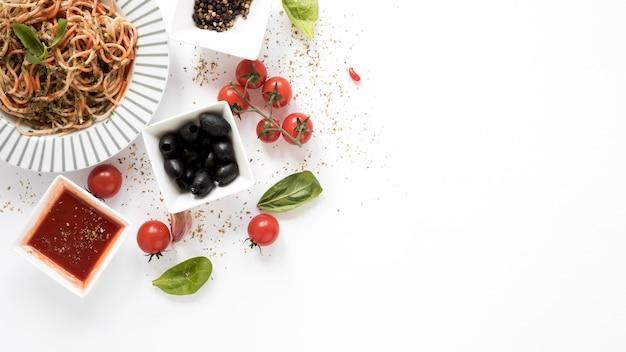 Vista dall'alto di spaghetti con oliva; pomodoro; foglia di basilico; erbe su sfondo bianco