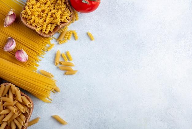 Vista dall'alto di spaghetti crudi con pasta cruda in ciotole con aglio e pomodori su una superficie grigia
