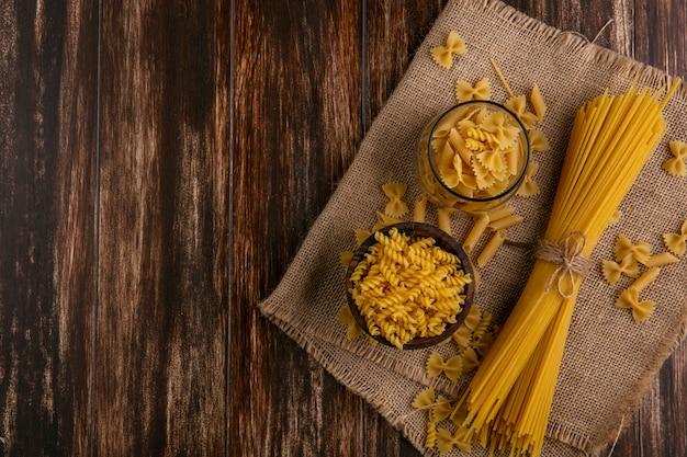Vista dall'alto di spaghetti crudi con pasta cruda su un tovagliolo beige su una superficie di legno