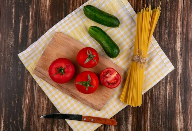 Vista dall'alto di spaghetti crudi con pomodori su un tagliere con un coltello e cetrioli su un asciugamano a scacchi giallo su una superficie di legno